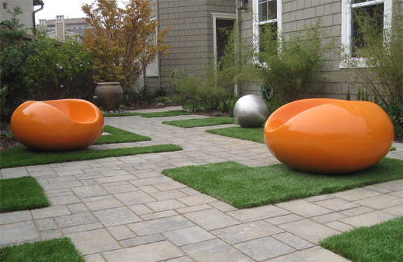 A CA modern garden path with pavers, synthetic turf, modern outdoor furniture, garden balls, and bamboo.